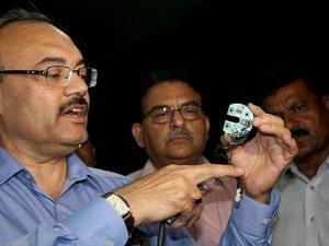 STF Additional SP Arvind Chaturvedi (blue shirt) showing chip and remote used by a petrol pump