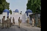 Security personnel stand guard at the main gate of the Pakistan High Commission in New Delhi
