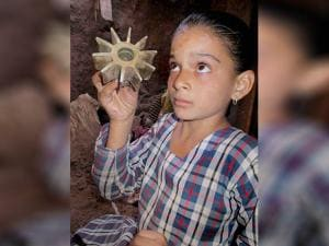 A small girl shows a mortar shell fired from across the LOC