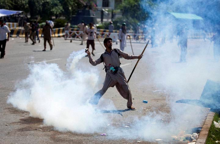Pakistani, protester, throws, tear gas, shell, back, towards, police, protest, Islamabad