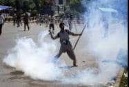A Pakistani protester throws tear gas shell back towards police during a protest in Islamabad