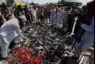 Pakistani protesters gather around a pile of empty tear gas canisters fired by police
