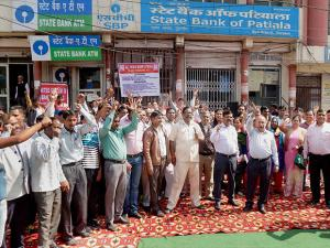 Bank employees hold a demonstration outside a bank during their nationwide strike in Gurugram