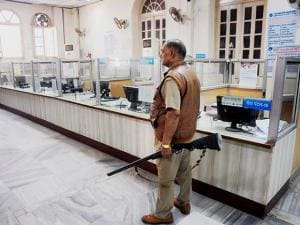 Security guard keeps vigil in a bank as the bank employees nation-wide go on a strike, in Allahabad