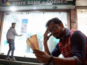 A man sits with Rupees 500 currency notes withdrawn from an ATM
