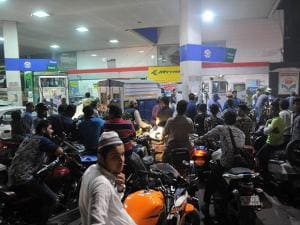 People crowd at a petrol pump to fill petrol 02