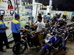 People crowd at a petrol pump to fill petrol