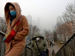 People wearing masks for protection against air pollution walk to a pedestrian overhead bridge in Beijing