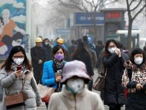 Women wearing protection masks walk on a street in Beijing as the capital of China is shrouded by heavy smog