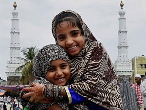 Muslim girls greet each other after offering Eid al-Fitr prayers at Walajah Big Mosque