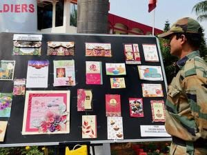 An Army jawan looks at the  on display of the Diwali greeting cards