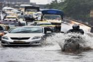 People wade through a flooded street after heavy downpour in Mumbai on Tuesday
