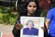 A girl holds a placard paying tribute to former President APJ Abdul Kalam