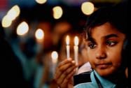 A School Child prays during a candle light vigil for the victims