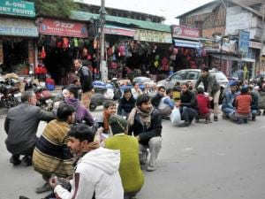 People come out of their shops and homes and sit in fear after an earthquake at Lal Chowk