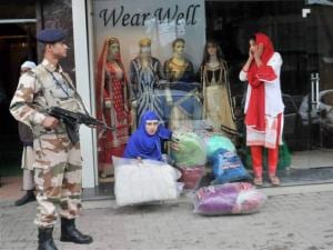 Women come out of  a shop while a jawan looks beside after an earthquake at Lal Chowk