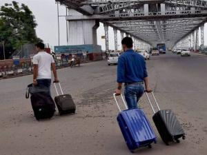 Passengers walk with their luggage at the almost deserted Howrah bridge
