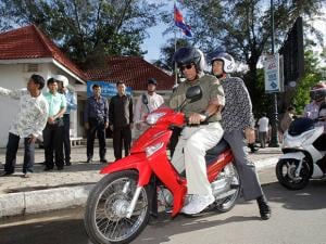Cambodia's Prime Minister Hun Sen drives a motorbike after a paying fine