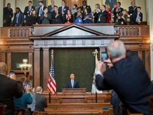 Politicians use their cellphone to photograph President Barack Obama as he takes the podium to address the Illinois General Assembly