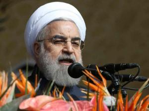 Iranian President Hassan Rouhani delivers a speech during a rally to commemorate the 37th anniversary of the Islamic revolution