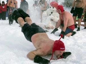 A man dives in the snow as Bonhomme buries another one in snow, at the annual carnival snow bath