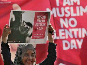 A Muslim girl displays posters  Muslims forbidden to celebrate Valentine's Day during a protest against Valentine's Day in Jakarta