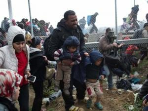 refugees on the Greek side of the border as they run away after Macedonian police fired tear gas at a group of the refugees and migrants who tried to push their way into Macedonia