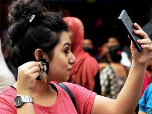 A woman taking the help of her phone while selecting a jewellery ahead of the upcoming Durga Puja