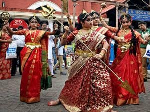 Girls dressed up as Goddess Durga enact the killing of demons during an event at a market ahead of Durga Puja festival