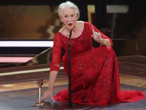 In this Feb. 6, 2016 photo British actress Helen Mirren kneels on stage during the 51st Golden Camera Award in Hamburg, Germany.  Mirren was awarded in the category 'Lif