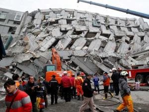 Rescue workers search a collapsed building from an early morning earthquake in Tainan, Taiwan, Saturday, Feb. 6, 2016. A powerful, shallow earthquake struck southern Ta