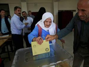 An elderly woman is helped to cast her vote in Cizre
