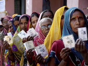 Women voters wait in a queue to cast their votes