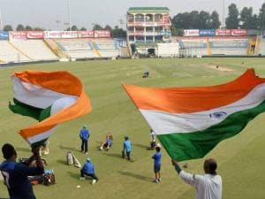Indian cricket team exercise in the field as fans hold flag