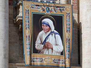 A tapestry picturing Mother Teresa hangs from the central balcony of St. Peter's Basilica