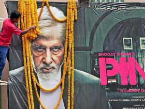 A poster of Amitabh Bachchan's next, being garlanded by one of his fans