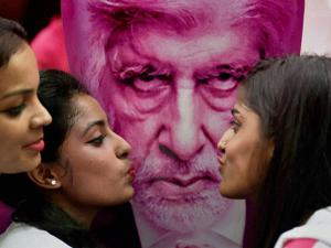 Amitabh Bachchan's fans pose in front of a poster of his upcomming movie
