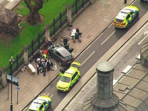 In this image taken from video  police officers gather around a car adjacent to  Houses of Parliament in London