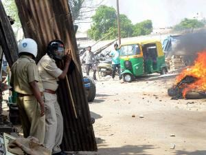 Policemen protecting themselves from stones throwing by agitated people during the during Municipal Corporation demolition drive at Bhimatalav Colony in Vadodara
