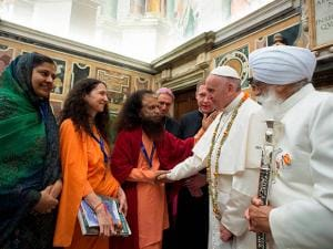 Pope Francis shakes hands with representatives of different religions during an inter religious meeting