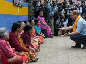 Britain's Prince Harry interacts with a group of local women while he visits the Golden temple in Patan Durbar in Patan, Nepal
