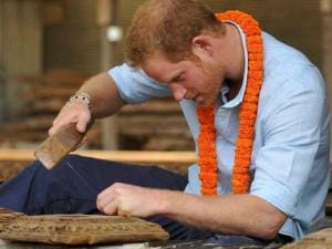 Britain's Prince Harry tries wood carving in heritage sites in Patan Durbar Square in the outskirts of Kathmandu