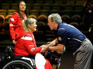 Former President George W. Bush, right, presents a gold medal in women's powerlifting to Canada's Christine Gauthier at the Invictus Games at Disney's ESPN Wide World of Sports