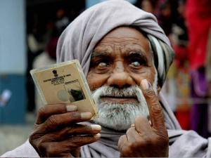 90-year-old Madho Ram showing his indelible ink marked finger and voter ID card after casting his vote