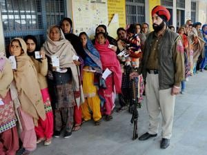 Women showing their voter ID cards as they stand in a queue to cast their votes