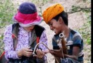 A foregin tourist interacts with local boy who plays traditional instruments during Pushkar Camel fair in Rajasthan