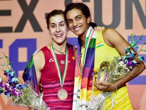 P V Sindhu , pictured here with her opponent Carolina Marin, celebrates after winning women's singles final