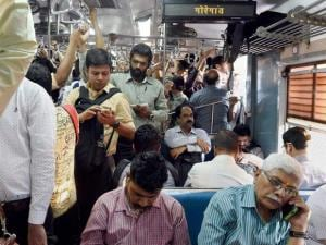 Commuters travel in a suburban local train of Western Railway on the eve of the Railway Budget
