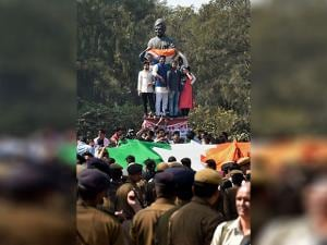 ABVP workers climb atop a Vivekananda statue during a their protest in DU's North Campus