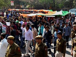 ABVP workers march with a giant tricolour during a protest in DU's North Campus